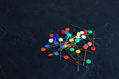 Decorative pins scattered on a dark background stock image