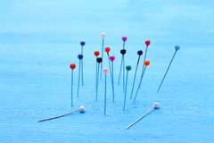 Decorative pins for sewing stuck into a blue board royalty free stock images