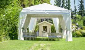 Decorative place for ceremonies or entertainments. Outdoor reception under tents and trees. Decorative place for ceremonies or entertainments. Outdoor reception Stock Photos