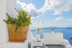 Decorative plants and elements of street design in mediteranian style, and Therasia on backdrop. Santorini island Stock Photo