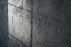 Decorative plaster. Artificial concrete. The texture of the gray concrete wall with a glint of light from the window. stock image