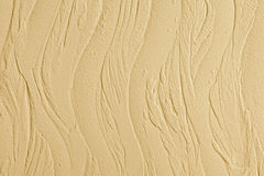 Decorative plaster. Wall stucco texture. In style waves, beige color. Stock Photography