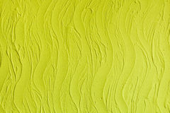 Decorative plaster. Wall stucco texture. In style waves, lemon yellow color. Stock Photos