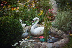 Decorative plastic flowers, swans and ducks in the artificial ga Stock Photos