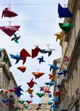 Decorative Plastic Pinwheels and Buildings. Decorative plastic pinwheels in multiple colors suspended from wires between buildings along a narrow street in Arles Stock Photography