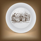 Decorative plate with drawing of old cottage Stock Photo