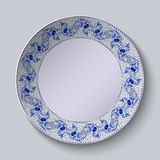 Decorative plate with floral pattern in blue and white space in the center. Stylized Gzhel. Royalty Free Stock Image