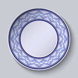 Decorative plate with painted blue floral pattern in ethnic style. Royalty Free Stock Image
