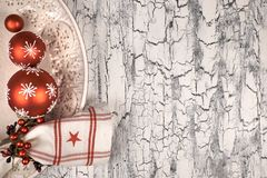 Decorative plate with red Christmas baubles on rustic background Stock Photo