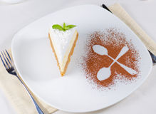 Decorative plating and presentation of cheesecake. Decorative plating and presentation of a slice of creamy cheesecake viewed from above with the outline of two Stock Image