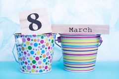 Decorative polka dots and stripes buckets, March 8. Wooden calendar and bucket on turquoise background royalty free stock photos