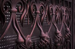 Decorative processing of metal forged colored gates in dark colors.  royalty free stock image