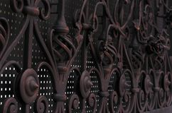 Decorative processing of metal forged gates in dark colors.  royalty free stock image