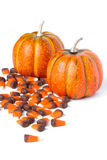 Decorative Pumpkins with Candy Corn on the side. Two Holiday pumpkins on a white background sprinkled with candy corn stock images