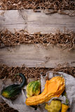 Decorative pumpkins over rustic wooden background. Autumn harvest, seasonal vegetables. Copy space, top view. Stock Photo