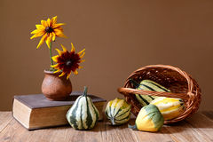 Decorative pumpkins and sunflowers in a vase