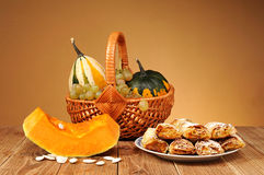 Decorative pumpkins in wicker baskets and pastries Royalty Free Stock Photos