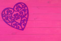 Decorative purple filigree heart on pink. Decorative purple filigree heart on an exotic bright pink wooden background with copy space for a Valentines or Stock Image