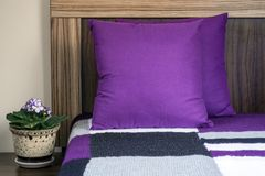 Decorative purple pillows and a knit blanket on a bed. Bedroom detail Royalty Free Stock Photography