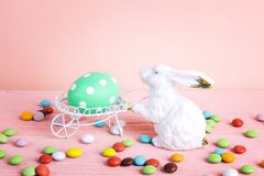Decorative rabbit with  Easter egg and sweets on pink background Stock Images
