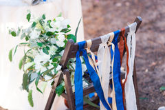Decorative red, blue and white ribbons on chair. Decorated chairs with red bows in a row. Royalty Free Stock Photography