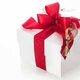 Decorative red bow on a gift box. Decorative red bow with a gold tassle and bauble highlight on a white gift box for celebrating Christmas, Valentines, birthday Stock Photography