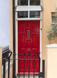 Decorative red door to the London house, typical architectural feature, London, United Kingdom.  Royalty Free Stock Photos