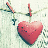 Decorative red heart and small metal key on a rope against the background of an old white board Royalty Free Stock Photography