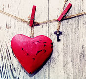 Decorative red heart and small metal key on a rope against the background of an old white board Stock Images