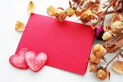 Decorative red hearts, blank red card with space for text and dry roses on a white surface Royalty Free Stock Photography