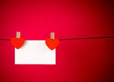 Decorative red hearts with greeting card hanging on red background, concept of valentine day Stock Images