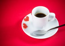Decorative red hearts near cup of coffee on red table, concept valentine day Stock Photo