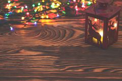 Decorative red metal lantern with a deer cutout lit by a glowing candle with christmas light and copyspace for Christmas Stock Photo
