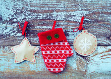 Decorative red mitten and Christmas tree decorations from paper on a rope against the background of the old removed board Royalty Free Stock Photos