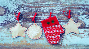 Decorative red mitten and Christmas tree decorations from paper on a rope against the background of the old removed board Royalty Free Stock Image