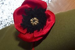 Decorative red poppy lying - on the rough fabric of the khaki Stock Photo