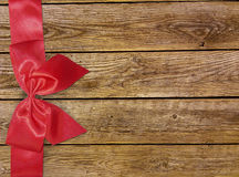 Decorative red ribbon and bow over wooden background. Holidays background with copyspace. Old wooden background with beautiful bow Royalty Free Stock Photography
