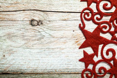 Decorative red star Christmas border. With curlicues and swirls on the right side of a rustic wooden background with copyspace for your Xmas greeting royalty free stock images