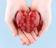 Decorative red stone heart in hands for Valentine's Day Stock Photography