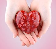 Decorative red stone heart in hands for Valentine's Day Stock Photo