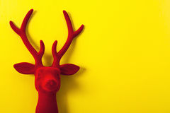 Decorative red velvet reindeer on a yellow background. Decorative Christmas happy reindeer red velvet on yellow background Royalty Free Stock Photo