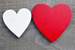 Decorative red and white wooden hearts on a grey wooden background.Two Valentine hearts.Saint Valentine`s Day or Love concept. Stock Photo
