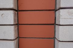 Decorative brickwork made of white and orange bricks Stock Images