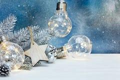 Decorative retro garland on silver christmas tree branch against. Decorative retro garland on silver christmas tree branch with wooden star against blue royalty free stock photos