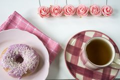 Flat lay pink breakfast with roses, cup of tea, napkin and donut on plate. stock photo