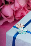 Decorative romantic present. Decorative wrapped present with decorative flowers and roses in background Stock Photo