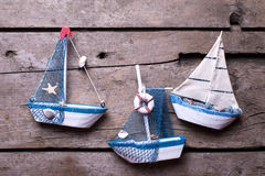 Decorative sailing boats on  aged  wooden background. Royalty Free Stock Photos