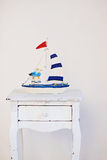 Decorative  sailing boats on wooden background. Sea decorations on the white commode. Decorative  sailing boats on antic wooden commode. Sea objects on wooden Royalty Free Stock Photo