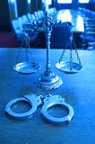 Decorative Scales of Justice in the Courtroom. Symbol of law and justice with handcuffs in the empty courtroom, FOCUS ON THE SCALES, blue tone Stock Photos
