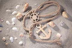Decorative sea anchor and steering wheel with rope and seashells on the sand . Top view. stock image